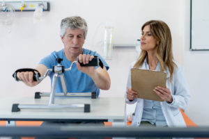 Senior male patient exercising his arms on machine while talking to occupational therapist