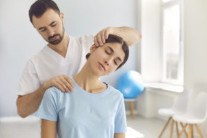 Licensed chiropractor doing neck adjustment to female patient in modern medical office