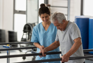 occupational therapist helping a senior patient while he walks using his hands to support his weight on the bars