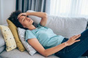 Sick young woman lying on the couch